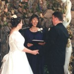 A photo of Carolyn Ringo ministering a wedding ceremony with the bride and groom.