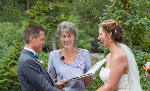 a photo of the minister, bride and groom laughing during the wedding ceremony